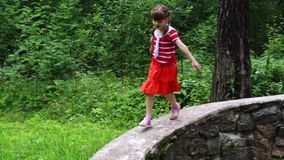 Little cute girl climbs and runs on stone wall stock video