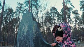Little cute girl in a colorful pink jacket draws with chalk on a blackboard in the form of a dinosaur on a children`s stock footage