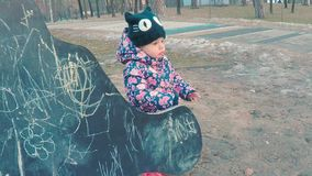Little cute girl in a colorful pink jacket draws with chalk on a blackboard in the form of a dinosaur on a children`s stock video