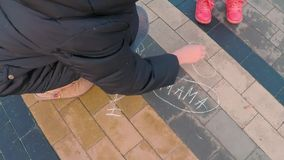 Little cute girl in a colorful pink jacket draws with a young mother with chalk on a pavement near the playground in a stock video