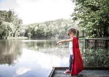 Little cute girl in costume of a super hero. Plays in the fresh air near the river on the wooden pier,the concept of a super hero and a childhood dream royalty free stock photo