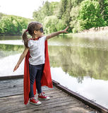 Little cute girl in costume of a super hero stock images