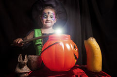 Little cute girl costumed as a witch spells a sweet pumpkin. Studio take Royalty Free Stock Photography