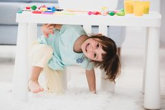 Little cute girl crawled under the table. The kid smiles, plays hide and seek.  royalty free stock photos