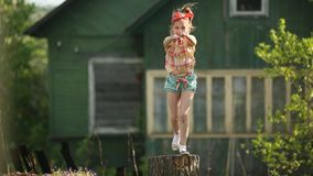 Little cute girl dancing on a stump in the yard of a country house. Happy.