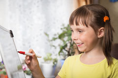 Little cute girl draws a marker of red color on a white board Royalty Free Stock Photo
