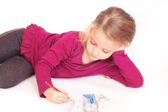 Little cute girl draws pencils lying on the floor Royalty Free Stock Images