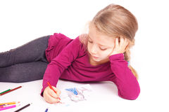 Little cute girl draws pencils lying on the floor Stock Images