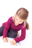 Little cute girl draws pencils sitting on the floor Stock Photos
