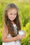 Little cute girl drinking a glass of milk outdoor summer. Little cute girl drinking a glass of milk in garden. Adorable curly kid having breakfast. Summer time Royalty Free Stock Photography