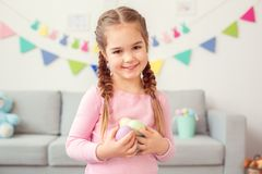 Little cute girl easter celebration at home concept standing holding eggs looking camera close-up royalty free stock photo