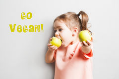 Little cute girl eating apple. inscription Go Vegan Royalty Free Stock Image