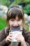 Little cute girl eating chocolate Stock Photography