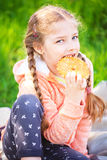 Little cute girl eating cookies. On nature background Royalty Free Stock Image