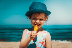 Little and cute girl eating ice cream on the beach. On vacation Stock Image