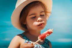 Little and cute girl eating ice cream on the beach. On vacation Stock Photography