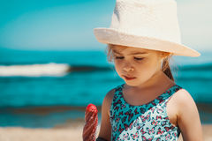 Little and cute girl eating ice cream on the beach. On vacation Stock Photo