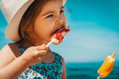 Little and cute girl eating ice cream on the beach. On vacation Royalty Free Stock Image