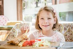 Little Cute Girl Eating Toast with Salad at Breakfast Stock Photography