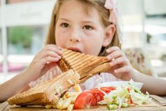 Little Cute Girl Eating Toast with Salad at Breakfast Stock Images