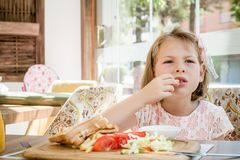 Little Cute Girl Eating Toast with Salad at Breakfast Stock Image