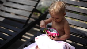 Little cute girl eats a dragon fruit outdoor. Little cute girl sitting on sunbed and eats a dragon fruit stock footage