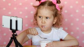 A little cute girl eats food and watches cartoons on the mobile phone. Child and gadgets, applications, internet, games.
