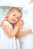 Second child. Little cute girl embracing her pregnant mother Stock Photos