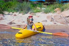 Little cute girl enjoy swimming on yellow kayak in Stock Photo