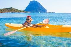 Little cute girl enjoy swimming on yellow kayak in Stock Photography