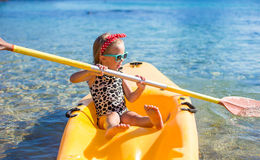 Little cute girl enjoy swimming on yellow kayak in Royalty Free Stock Photos