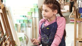 Beautiful little girl painting on the easel using oil paints at the art studio. Little cute girl enjoying painting on easel at the art studio looking stock image
