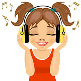 Little cute girl enjoys listening to music with headphones. On white background Royalty Free Stock Photo