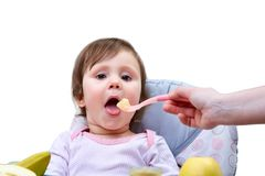 A little cute girl is fed with a spoon of fruit puree on the white background. A little cute girl is fed by her mom with a spoon full of fruit puree, sitting on royalty free stock image