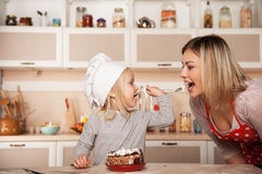Little cute girl feeding her mother cake Royalty Free Stock Photography