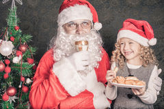 Little cute girl feeding Santa cookies and milk at Christmas Royalty Free Stock Photography
