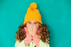 Little cute girl feeling cold. Little cute amazed girl wearing warm cap and scarf feeling cold Royalty Free Stock Image