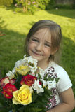 Little cute girl with flowers in garden. Girl with flowers in the garden while sun is setting in the background Royalty Free Stock Photo