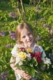 Little cute girl with flowers in garden. Girl with flowers in the garden while sun is setting in the background Royalty Free Stock Image