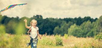 Little cute girl flying a kite. In a meadow on a sunny day Royalty Free Stock Photography
