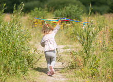 Little cute girl flying a kite Stock Images