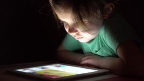Little cute girl in full darkness watching tablet. Home stock video footage