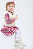 Little cute girl in fur boots sits on cube Royalty Free Stock Photo