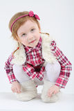 Little cute girl in fur vest and boots sits and looks up Stock Photography