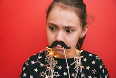 Little cute girl with a garland around her neck holding a mustache props on a red background royalty free stock images