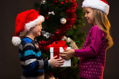 Little cute girl giving gift box to her younger brother. Stock Photo