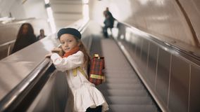 Little cute girl going upstairs by escalator in subway. Beautiful female child clothing in french style with backpack. Little cute girl going upstairs by the stock video