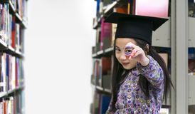 The little cute girl with the graduation cap and diploma paper. Stands and smile in the shelf of books background Stock Photo