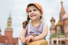 Little cute girl in a hat with a bag. On the background of the Kremlin stock images