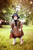 Little cute girl in hat and cloak  with handbag in autmn pa Royalty Free Stock Images
